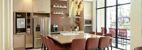 AMLI on Riverside resident kitchen with floor to ceiling windows and stainless steel appliances with big table for gathering