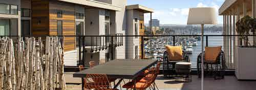 Daytime view of exposed rooftop deck overlooking the marina with a long dining table and orange chairs at AMLI Marina Del Rey