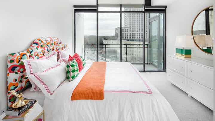 AMLI 3464 bedroom with floor to ceiling windows and a city view with white walls and bedding with bright coral and teal decor