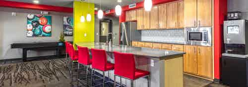 Interior of the Java Cafe amenity space at AMLI 535 with kitchen microwave fridge microwave sink and coffee machine with red chairs and shuffle board