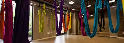 The aerial yoga studio at AMLI Dadeland with multiple vibrant colored hammocks hanging from the ceiling
