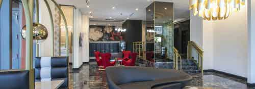 AMLI Midtown Miami with modern black sofa and gold chandelier and mirrored pillar and mail boxes with red chairs at back