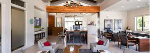 AMLI Covered Bridge leasing office with light tile flooring, lounge chairs with pillows, and a wooden accent beam
