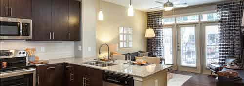AMLI West Plano kitchen and living room with dark wood cabinets and floors with barstools and modern hanging light fixtures