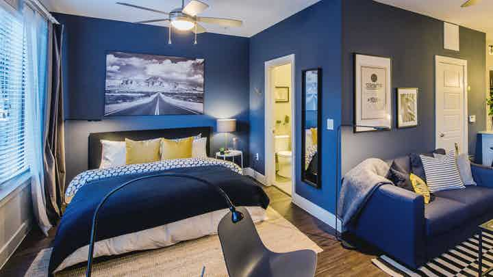 Interior view of AMLI at the Ballpark furnished studio apartment with bedroom and living room areas with blue walls