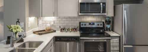 AMLI Eastside kitchen with stainless l appliances and quartz countertops with white cabinets and white tile backsplash