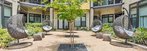 AMLI 5350 courtyard with circular grey wicker chairs and vibrant green bushes and trees with building facade in background