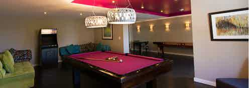 Interior game lounge at AMLI Dadeland with vibrant colored billiards table, arcade game and plush seating
