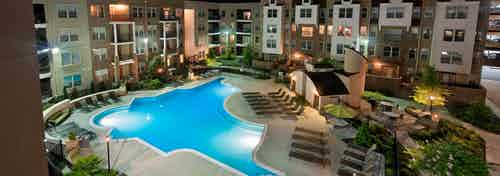 Ariel view of AMLI Lindbergh apartment community with a large well lit pool and surrounding lounge chairs at nighttime