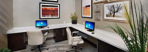 Interior of business center at AMLI Doral apartments with computer stations, desk chairs and artwork on the wall