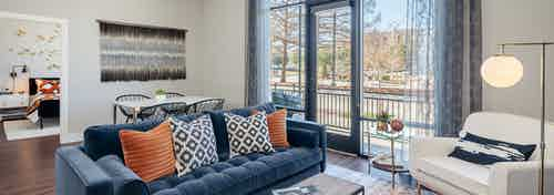 Living room at AMLI Addison with Kember plank flooring and large glass doors leading to balcony with white and blue seating