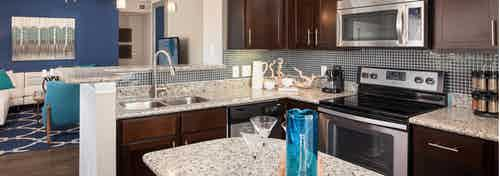 AMLI Memorial Heights apartment kitchen with dark wood cabinets and tile backsplash and granite island and countertops