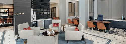 AMLI Addison leasing office with white patterned flooring and four white sofa chairs with leasing desks in background
