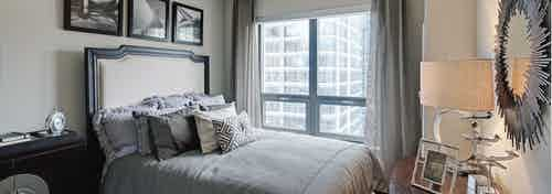 Elegant bedroom at AMLI River North with a large grey bed in front of a window with flowing curtains and a daytime city view