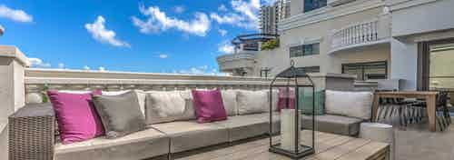 Sky view of the AMLI Joya apartment's rooftop resident lounge with sectional outdoor sofa and magenta accent pillows