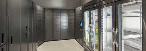 AMLI Downtown Amazon package room with gray metal lockers of varying sizes and two steel refrigerators for perishable packages
