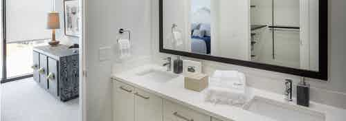 Interior of bathroom at AMLI 3464 with double vanity sink and white cabinets with open door leading to bedroom