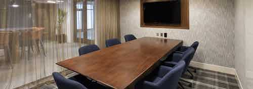 Interior of conference room with large table and chairs, big screen TV and sheer curtains at AMLI Marina Del Rey apartments