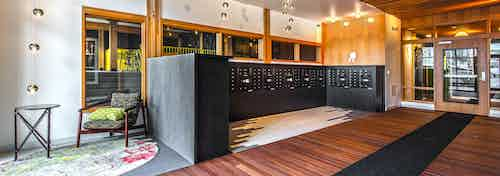 One of two resident mailbox areas at AMLI Wallingford with wooden floors and dark mailboxes and seating area