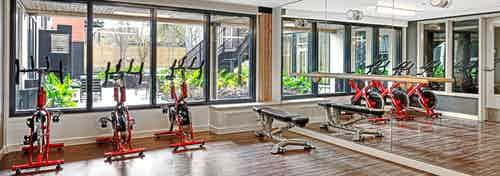 Interior of the Yoga Room at AMLI Wallingford with spin bikes free weights ballet bar and fitness on demand