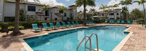Daytime view of AMLI Toscana Place swimming pool with lush palm trees, lounge chairs and view of building exterior