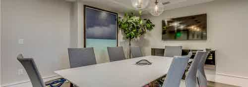 Interior conference room space at AMLI Joya with rectangular conference table and chairs, mounted tv and modern decor