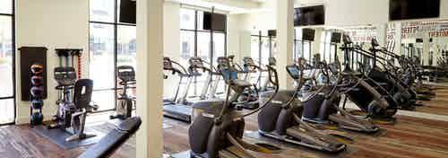 AMLI on Riverside fitness center with exercise machines facing floor to ceiling windows and large TVs hanging on the walls