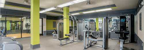Interior of the fitness center at AMLI Old 4th Ward apartment with treadmills and weight machines and vibrant walls