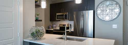 AMLI South Shore apartment kitchen with stainless steel appliances and quartz countertops with light ceramic tile backsplash