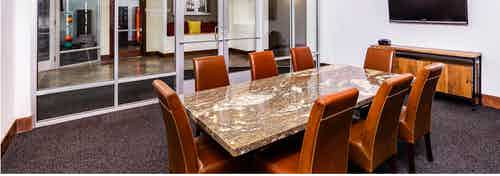 Interior view of a conference room at AMLI Park Avenue apartments with a granite table with padded chairs and a television