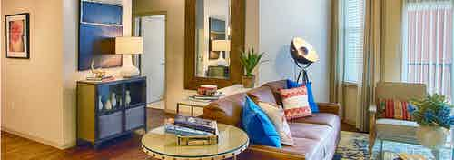 Interior view of a living room at AMLI Denargo Market apartments with lamps and a couch and chair and a look in the bedroom