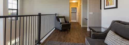Interior of AMLI Covered Bridge townhome second floor hallway with a seating area and dark brown plank flooring