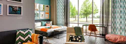 Bedroom at AMLI at Mueller with large floor to ceiling windows and dark wood floors with orange and blue decor accents