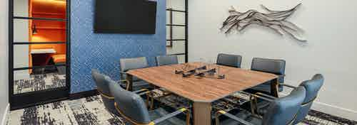 AMLI Addison resident conference room with large wooden desk and eight surrounding leather chairs with patterned carpet floor