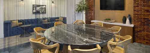 Interior of AMLI Marina Del Rey apartment conference room with round marble table, glass walls with sheer curtains and TV