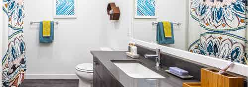 AMLI Wallingford apartment bathroom with dark quartz counter tops colorful towels and shower curtain