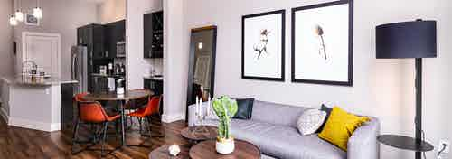 Interior of furnished living room, round dining table and kitchen with dark cabinets at AMLI Littleton Village apartments