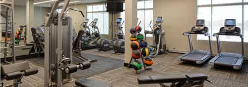 Fitness center at AMLI Deerfield with various cardio and weight machines including treadmills and elliptical machines