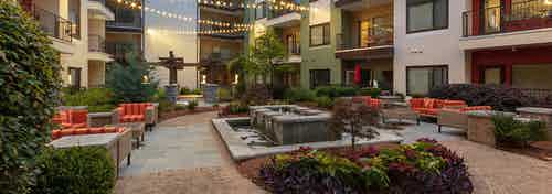 Nighttime exterior of AMLI Ponce Park courtyard with sitting area and fountain and hanging lights with colorful flowers