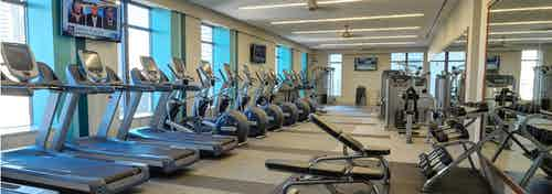 AMLI River North fitness center with treadmills along the wall and an area with shelved dumbbells in front of a mirror