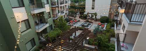 Overhead dusk view of AMLI Ponce Park courtyard  with sitting area and fountainand lit hanging lights