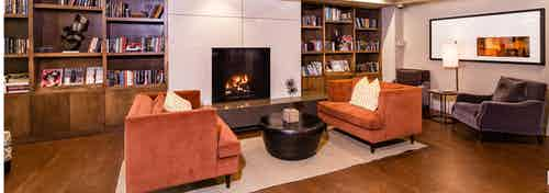 Interior view of library study lounge with two orange suede sofas, bookshelves and fireplace at AMLI RidgeGate apartments
