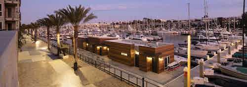 Evening view of walking promenade adorned with palm trees, lit up boat house facing marina at AMLI Marina Del Rey apartments
