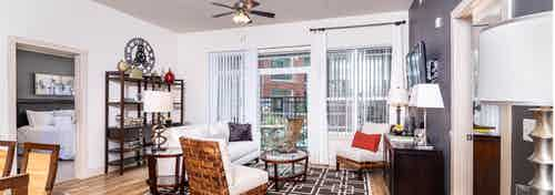 A living room at AMLI Park Avenue apartments with a white couch and a shelves and lamps and a television and a balcony door