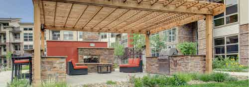 An outdoor barbecue area at AMLI Interlocken apartments with a large wooden awning over grills with several seating areas