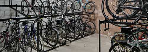 View of roughly twenty resident bicycles in a well lit storage area with cement flooring and white walls at AMLI Evanston