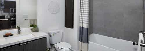 Interior of AMLI Park Broadway apartment bathroom with quartz countertop and large soaking tub with grey tile surround