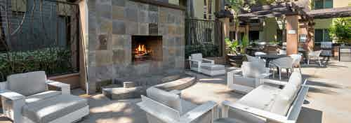 Large outdoor fireplace with cushioned lounge seating by outdoor grilling area at AMLI Warner Center apartments