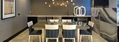 Interior of AMLI Deerfield gourmet kitchen with large dining table and blue and white chairs with decorative chandelier