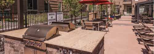 Barbeque area at AMLI Cherry Creek apartments with two grills and ample surrounding counter top are and chairs and tables